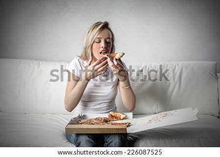Eating a tasty slice of pizza  - stock photo