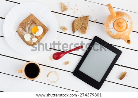 Eating and E-Reading. Buttered Toast with a Boiled Egg and Black Coffee - stock photo