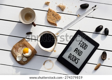 Eating and E-Reading. Buttered Toast with a Boiled Egg, Olives and Black Coffee. FOOD AND BOOKS Text Included - stock photo
