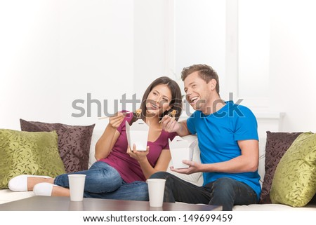 Eating Asian food. Beautiful couple eating Asian food from food containers and looking away while sitting on the couch - stock photo