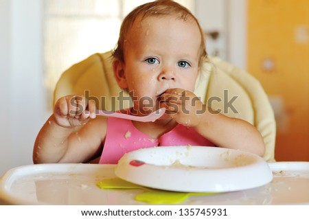 eating baby girl with dirty face - stock photo