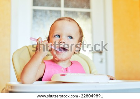 eating baby girl with spoon - stock photo