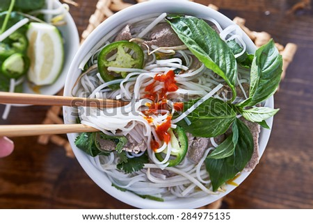 eating beef pho with spicy sriracha sauce shot top down - stock photo