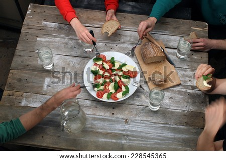 Eating caprese salad with friends, top view on rustic table with hands, bread and big plate with mozzarella, tomatoes and basil leaves (also available as footage) - stock photo
