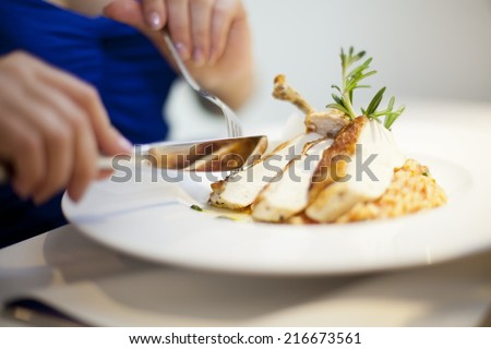 eating chichen from plate with fork and knife woman hands