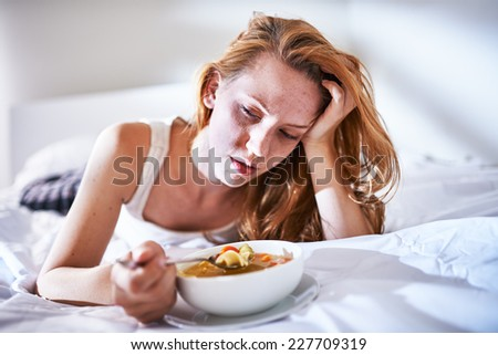 eating chicken noodle soup in bed while sick - stock photo