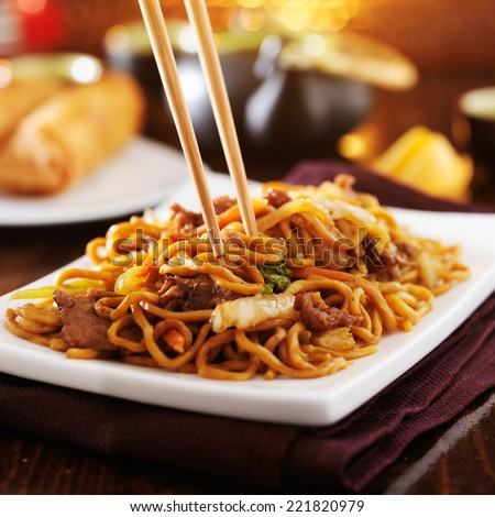 eating chinese beef lo mein with chopsticks - stock photo