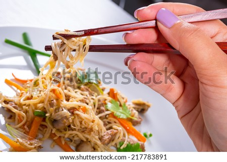 Eating chinese noodles with chopsticks - stock photo
