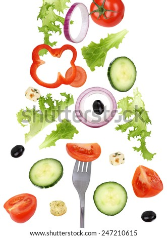 Eating falling green salad with fork, tomatoes, Feta cheese, onion, olives and cucumber - stock photo