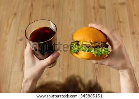 Eating Fast Food. Closeup Of Man's Hands Holding Classic American Hamburger And Glass Of Soda. Dinner At Restaurant. Point Of View. Nutrition - stock photo