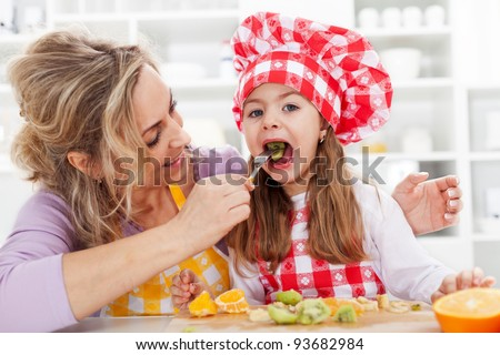 Eating fresh fruits is healthy - woman and little girl in the kitchen - stock photo