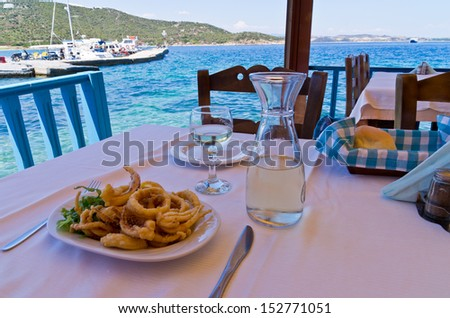 Eating fried squid and drinking white wine in a shade of a typical greek taverna by the harbor, Amoulani island, Greece - stock photo
