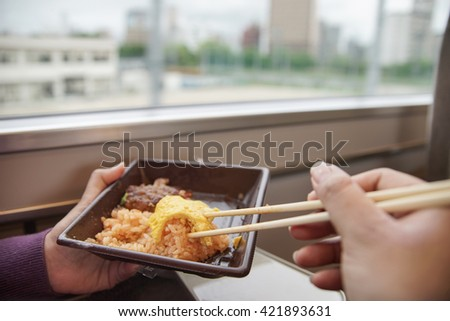 eating homemade food from plastic container while traveling by train