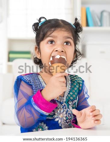 Eating ice cream. Cute Indian Asian girl enjoying an ice cream. Beautiful child model at home. - stock photo