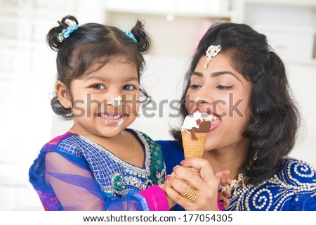 Eating ice-cream. Happy Asian India family sharing ice-cream at home. Beautiful Indian child feeding mother. - stock photo