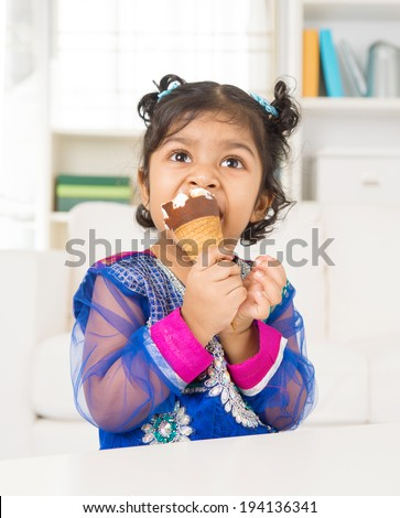 Eating ice cream. Indian Asian girl enjoying an ice cream. Beautiful child model at home. - stock photo