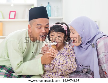 Eating ice cream. Muslim family sharing an ice cream. Beautiful Southeast Asian family living lifestyle at home. - stock photo