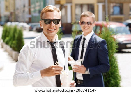Eating on go. Young happy man standing on background of another with Chinese fast food.