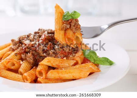 Eating Penne Rigate Bolognese or Bolognaise sauce noodles pasta meal on a plate - stock photo