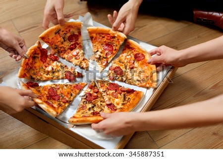 Eating Pizza. Group Of Friends Sharing Pizza Together. People Hands Taking Slices Of Pepperoni Pizza.  Fast Food, Friendship, Leisure, Lifestyle. - stock photo
