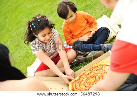 Eating pizza, picnic, family outdoor - stock photo