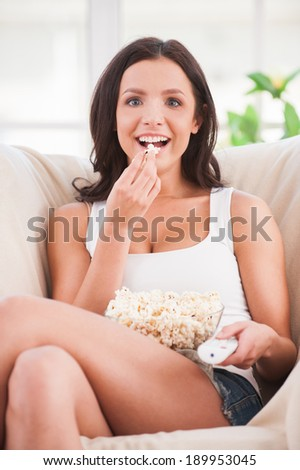 Eating popcorn. Beautiful young woman eating popcorn and watching movie while sitting on sofa - stock photo