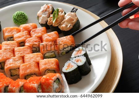 Eating salmon roll sushi in japanese restaurant, hand with chopsticks closeup. Female has dinner
