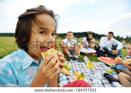 Eating snack sandwiches and having picnic on green grass meadow in nature