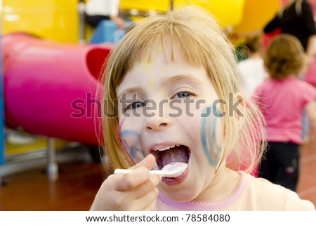 eating spoon funny girl playground smiling blond open mouth