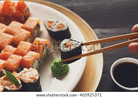 Eating sushi rolls. Japanese food restaurant, maki gunkan plate or platter set. Closeup of hand with chopsticks taking roll. Ginger, soy, wasabi dish at black rustic wood background. - stock photo