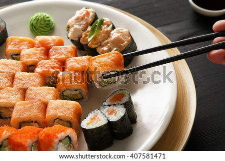 Eating sushi rolls. Japanese food restaurant, sushi maki gunkan roll plate or platter set. Closeup of hand with chopsticks taking roll. Ginger, soy, wasabi. Sushi at black rustic wood background. - stock photo