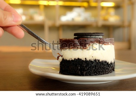 eating the chocolate cheesecake on white plate.  Over wooden table.Image has a warm tone  and some noise added. - stock photo