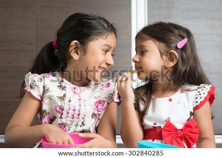 Eating traditional snack murukku. Cute Indian Asian girls enjoying food. Beautiful children model at home. - stock photo