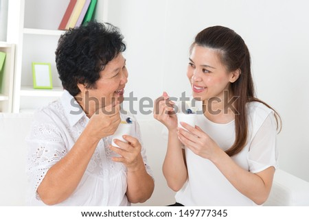 Eating yoghurt . Happy Asian family eating yogurt at home. Beautiful senior mother and adult daughter, healthcare concept. - stock photo