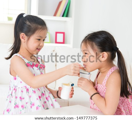 Eating yogurt. Happy Asian children eating yoghurt at home. Beautiful sisters . Healthcare concept. - stock photo