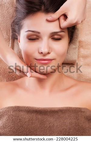 eautiful young relaxed woman enjoy receiving face massage at spa saloon - stock photo