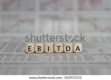 EBITDA word built with letter cubes on newspaper background - stock photo