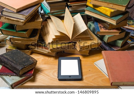 Ebook and old books on table - stock photo