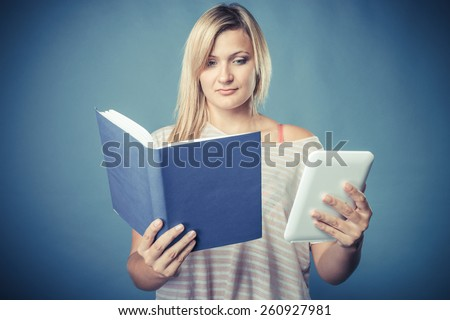 Ebook vs book. Young woman using tablet computer reading. Female with traditional book and e-book reader touchpad pc blue background. Vintage filter - stock photo