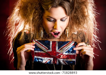 Eccentric British woman holding a purse with the Union Flag - stock photo