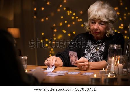 Eccentric elderly woman reading magic tarot cards - stock photo