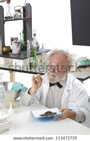 Eccentric senior scientist in lab holds pen and clipboard. High key, white background, vertical, copy space.