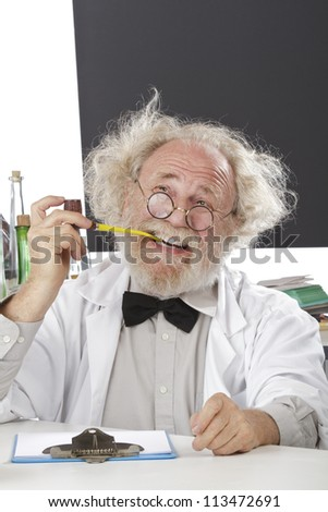 Eccentric senior scientist in lab holds pipe, thinks of ideas. HIgh key, vertical, copy space. - stock photo