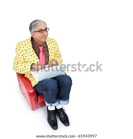 Eccentric  senior sitting and typing on his laptop. - stock photo