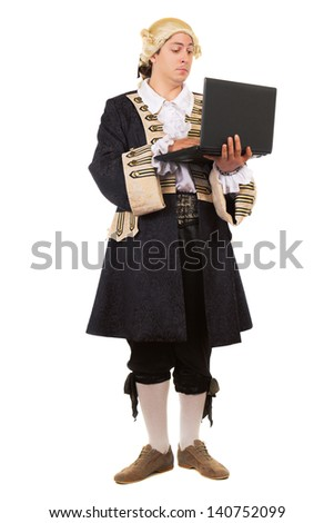 Eccentric young man in medieval costume posing with a laptop. Isolated on white
