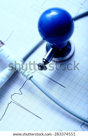 ECG chart, electrode and the cable on the desktop of doctor - stock photo