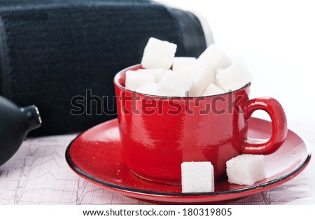 ECG diagram and red cup filled with sugar - stock photo