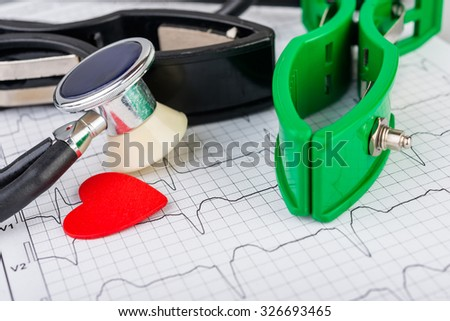 ECG electrodes and stethoscope on the background of the electrocardiogram close up. Medical background. - stock photo