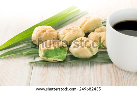 Eclair Pandanus leaf cream on Pandanus leaf with black coffe cup - stock photo