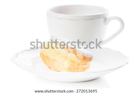 Eclair with powdered sugar filled custard on a white plate with an elegant fork and cup of tea - stock photo